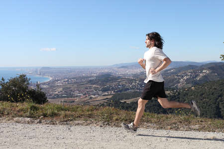 Man running in the mountain with whole Barcelona city in the background photo