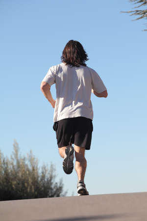 Back view of a man running on a road with the sky in the background photo