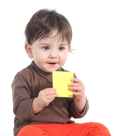 Baby holding and showing a blank yellow note on a white isolated background                photo