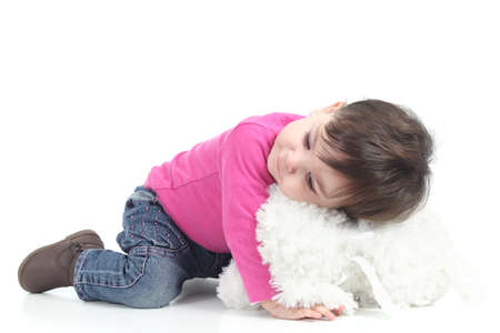 Baby hugging a teddy bear on a white isolated background               photo