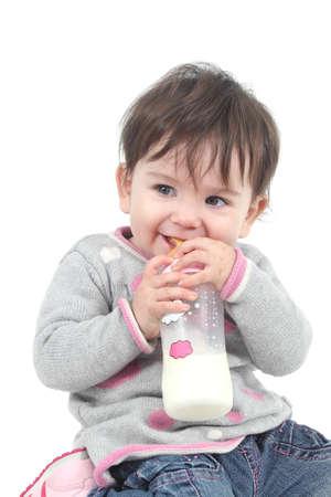 teteros: Bebé con un biberón en la boca en un fondo blanco aislado Foto de archivo