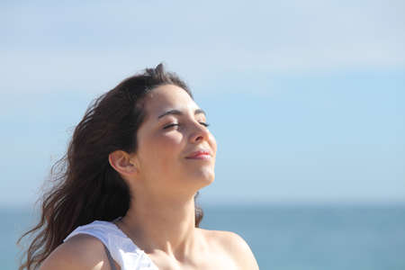 breath: Beautiful girl breathing on the beach with the sea in the background Stock Photo