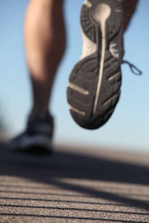 Unfocused man shoes running on the asphalt with the sky in the background photo