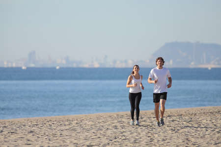 Woman and man running on the beach towards the sea with Barcelona city in the background  photo