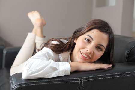 Beautiful teenager lying on a couch at home looking at camera              Stock Photo - 18230385