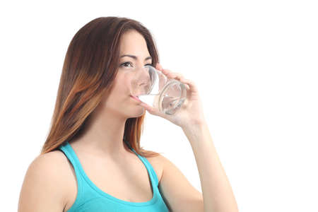Woman drinking water from a glass on a white isolated background               photo
