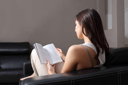 Beautiful woman at home sitting on a couch reading a book  Back view             photo