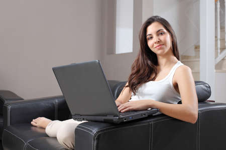 Beautiful woman at home sitting on a couch with a laptop and looking at camera              photo