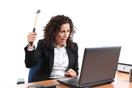 impatience: Mature businesswoman trying to destroy a laptop with a hammer in an office on a white isolated background             Stock Photo