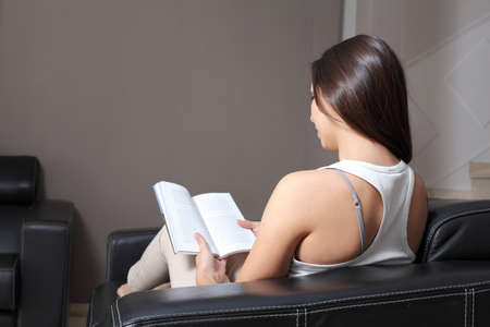 student reading: Back view of a beautiful woman at home sitting on a couch reading a book.