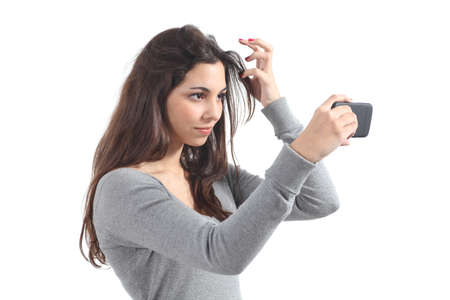 Beautiful teenager primping her hair using her phone like a mirror         photo