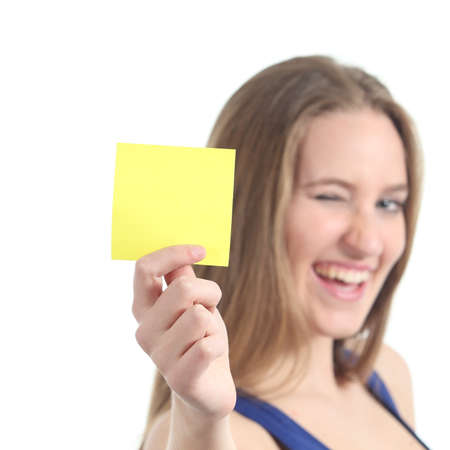Woman winking and showing a blank yellow paper note isolated on a white background             photo