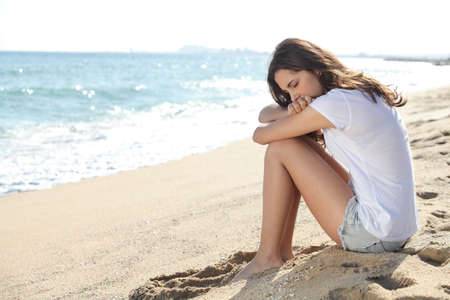 Portrait of a worried girl sitting on the beach with the sea in the background      photo