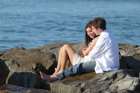 romanticism: Couple flirting and hugging sitting on a stone with the sea in the background