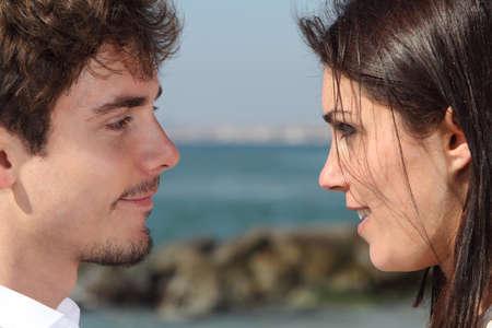mujer mirando el horizonte: Primer plano de una pareja que busca unos a otros con el amor con el mar de fondo