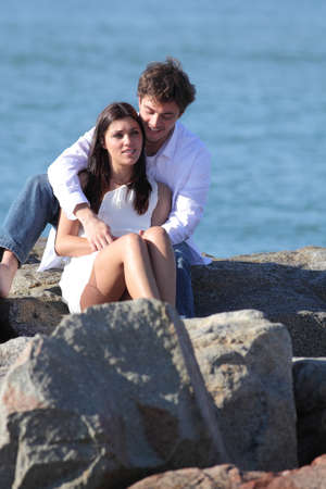Affectionate couple flirting and hugging on a stone on the beach with the sea in the background photo
