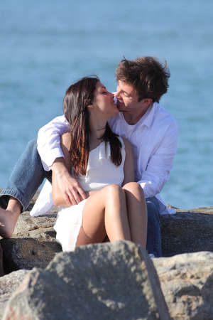 Couple kissing with love beside the sea sitting on a stone with the sea in the background photo