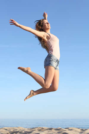Beautiful woman jumping happy on the beach with a blue sky in the background photo