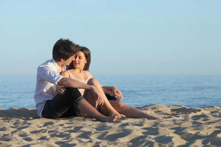 Couple flirting sitting on the sand of the beach with the sea in the background             photo