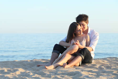 Couple embracing sitting on the sand of the beach with the sea in the background  photo