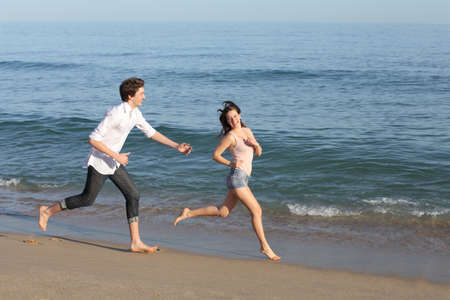 Couple playing and running on the beach shore near the water                photo