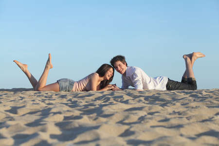 Couple laughing resting on the sand of a beach with the sky in the background photo