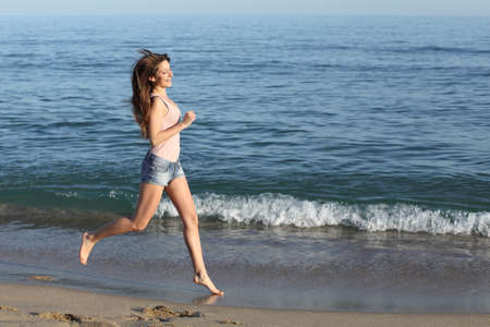 Beautiful casual woman running alone on the beach shore near the water                photo