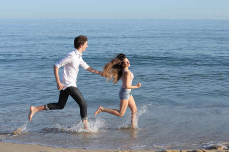 Couple chasing and running on the beach shore splashing water          photo