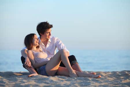 mujer mirando el horizonte: Pareja sentada y riendo en la arena de la playa al atardecer con el mar de fondo