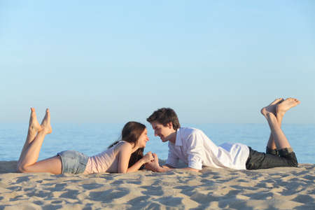 barefoot teens: Couple dating and resting on the beach sand with the blue sky in the background