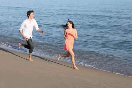 Couple of teenagers running and flirting on the beach shore near the water                photo