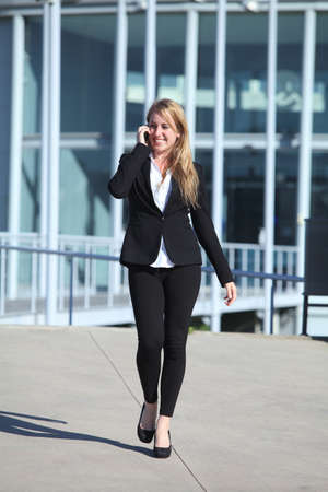 Happy businesswoman on the mobile phone walking with an office building in the background                photo
