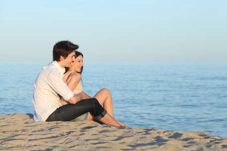 Couple cuddling sitting on the sand of the beach watching the sea     Stock Photo