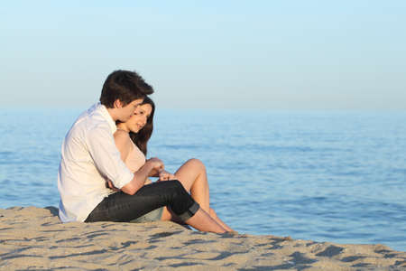 first love: Couple hugging sitting on the sand of the beach in front the sea