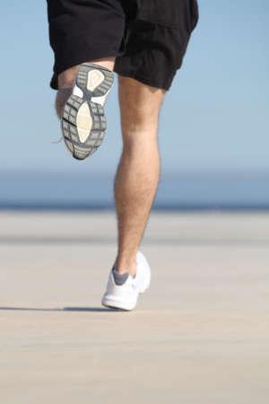 piernas hombre: Las piernas del hombre desenfocado que se ejecutan en el hormig�n de un mar con el cielo en el fondo