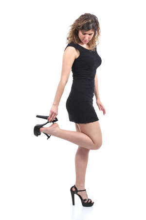 Beautiful woman wearing a black dress putting on or taking off heels isolated on a white background     photo