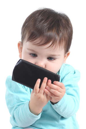 Casual baby watching attentive a mobile phone isolated on a white background
