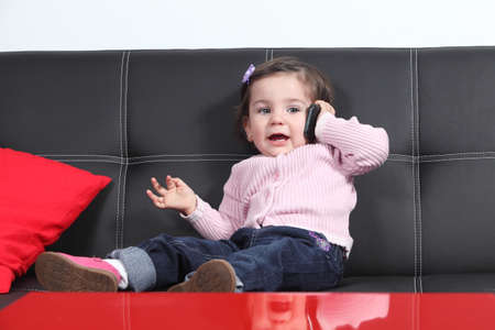 conversating: Casual baby taking a conversation with a mobile phone sitting on a black couch at home