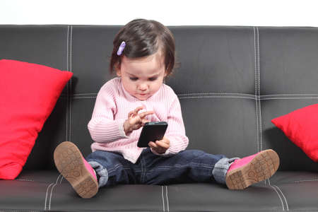 gaming: Casual baby sitting on a couch at home playing and touching a mobile phone