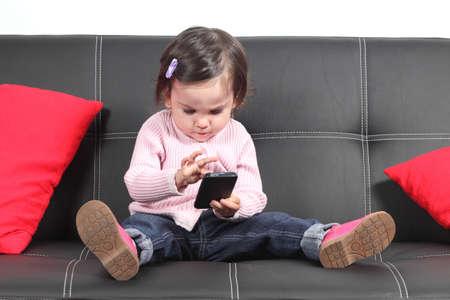 mobiele telefoons: Casual baby zitten op een bank thuis spelen en het aanraken van een mobiele telefoon
