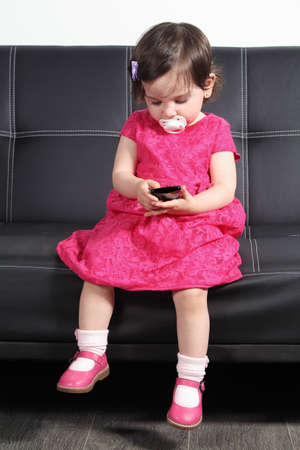 Bel bambino seduto su un divano nero in casa a giocare con un telefono intelligente
