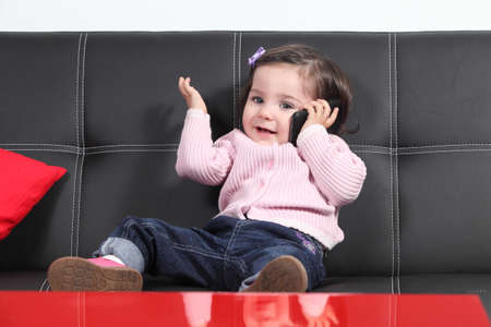Casual baby playing happy with a mobile phone sitting on a black couch at home photo