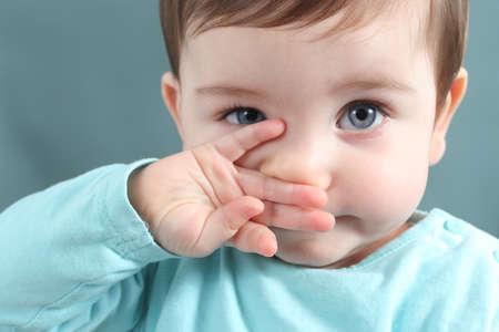 occhi grandi: Primo piano di una bambina guardando la fotocamera con un grande occhi blu con uno sfondo sfocato verde