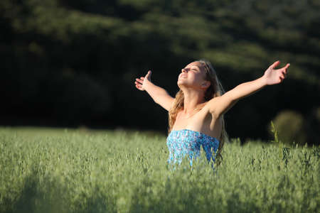 Beautiful teenager girl breathing happy with raised arms in a green meadow with a dark background photo