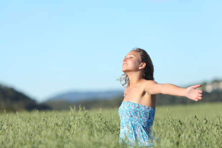 Beautiful woman breathing happy with raised arms in a green oat meadow with the blue sky in the background