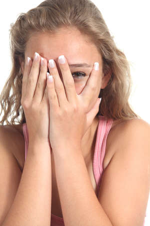 peeking: Beautiful blonde teenager girl peeking the eye through her hands isolated on a white background Stock Photo