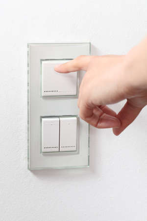 operate: Woman hand operating a light switch Stock Photo