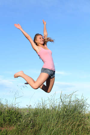 euphoric: Blonde teenager girl jumping happy in the mountain with the blue sky in the background