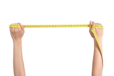 cinta de medir: Mano hermosa de la mujer estirando una cinta m?ica sobre un fondo blanco aislado