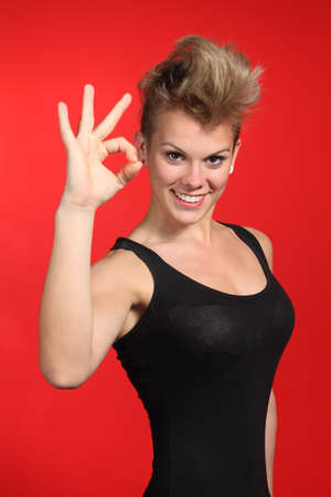 Beautiful fashion woman making ok gesture with a red background         photo